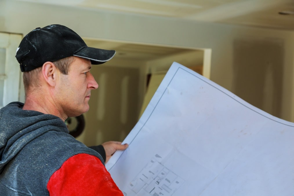 contracator looking at house plan