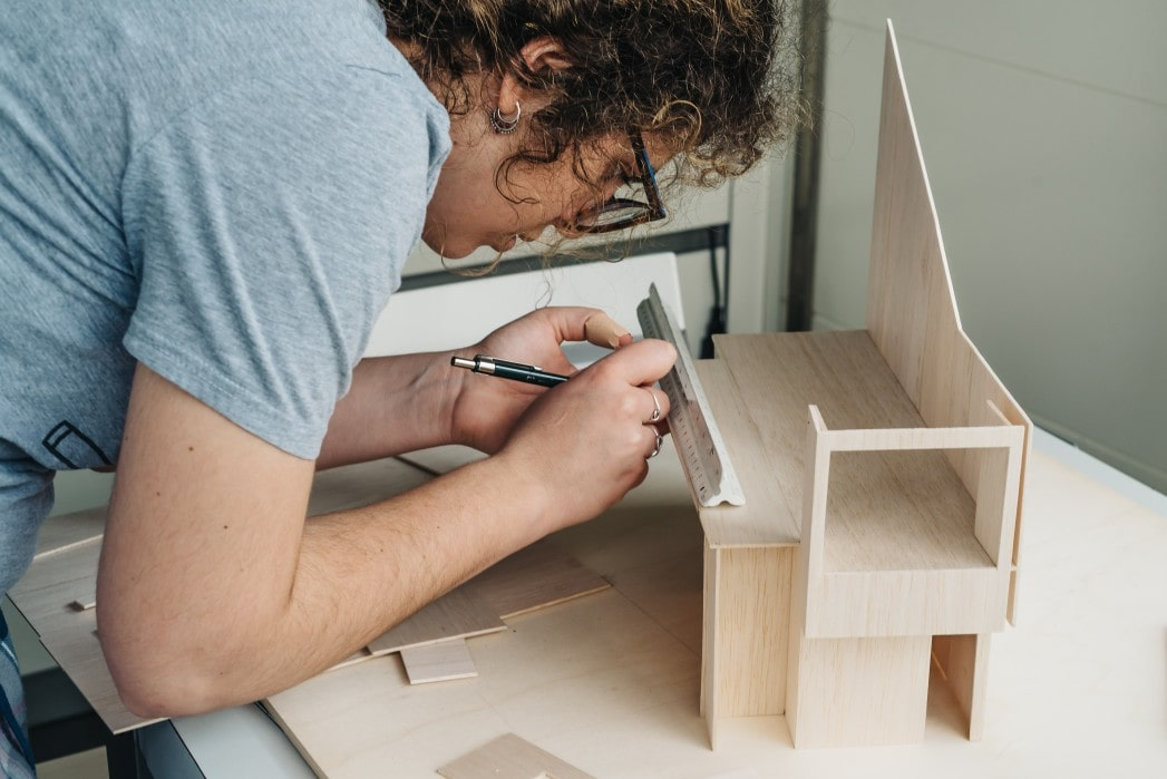 woman studying a model of a house being built